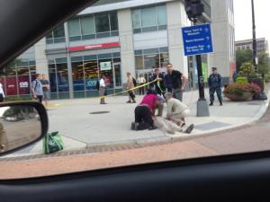 My husband (back center) unravels police line tape for bleeding victim on the corner. Photo Credit: TimHogan@twitter.com